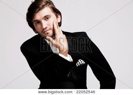 elegant young man in black tuxedo, portrait, studio shot