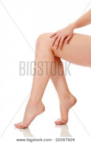 Uma mão tocando as pernas da mulher bonita, isoladas no branco