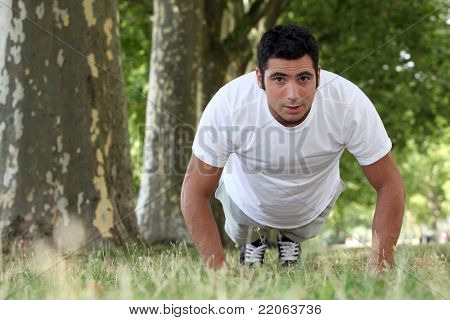 muscular man doing push-ups in a park