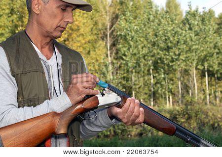 Man loading cartridges into a shotgun