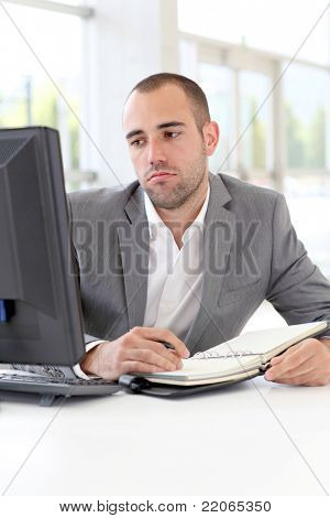 Businessman writing on agenda with bored look