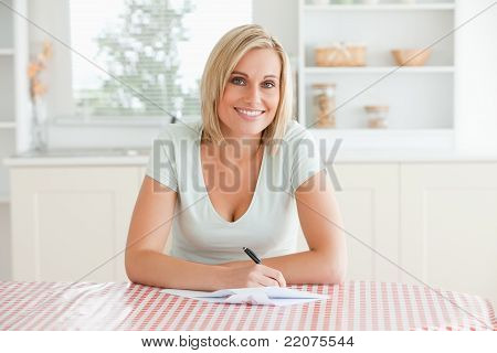 Woman Sitting At A Table Writing A Letter Looking Into Camera