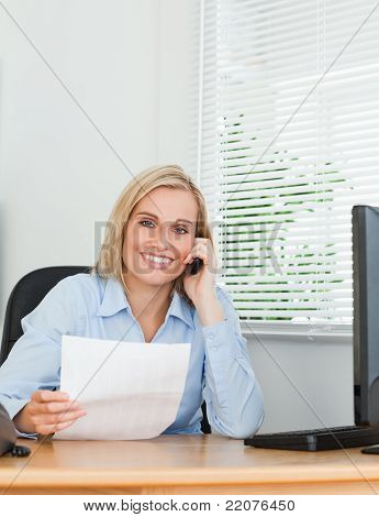 Portrait Of A Businesswoman Looking Up From A Letter Into Camera While Phoning