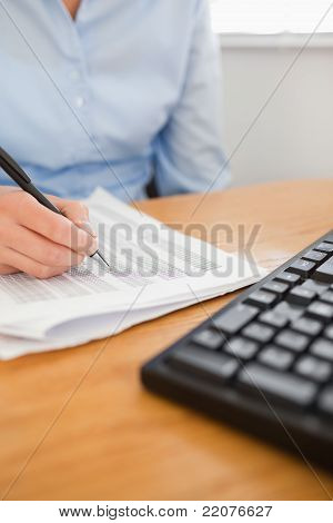 Businesswoman With Pen Going Through Numbers