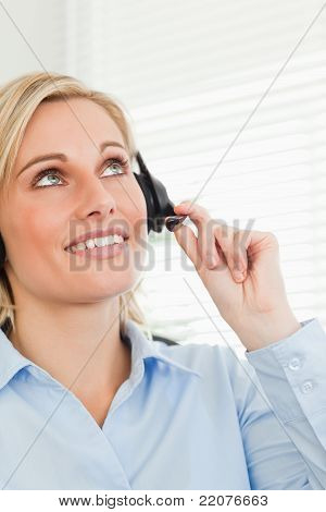 Smiling Businesswoman With Headset Looking At The Ceiling