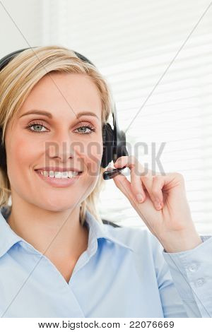 Smiling Businesswoman With Headset Looking Into Camera