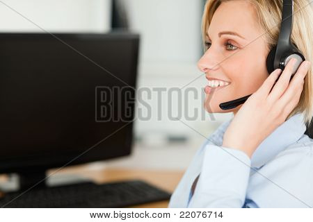 Portrait Of A Smiling Blonde Businesswoman With Headset Working With Computer Looking Elsewhere
