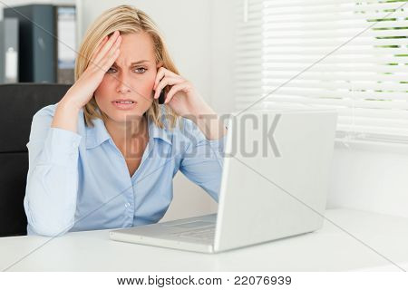 Frustrated Businesswoman Sitting In Front Of Her Notebook On Phone