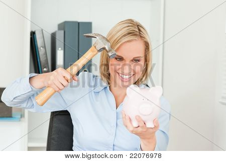 Smiling Blonde Woman Wanting To Destroy Her Piggy Bank