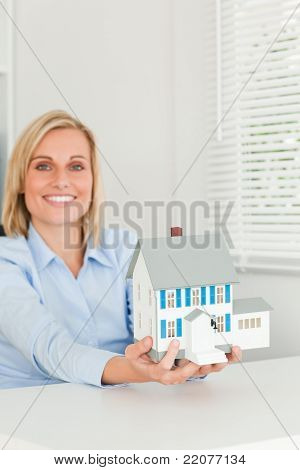 Smiling Businesswoman Showing Model House Looks Into Camera