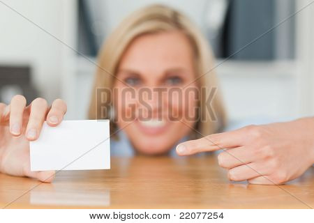 Businesswoman Pointing At A Card Crouching Behind Her Desk Looks Itno Camera