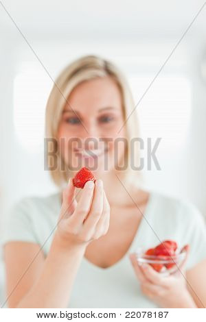 Woman Looking At Strawberry With Pleasure