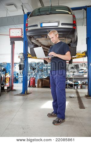 Full length portrait of young mechanic using laptop in his auto repair shop