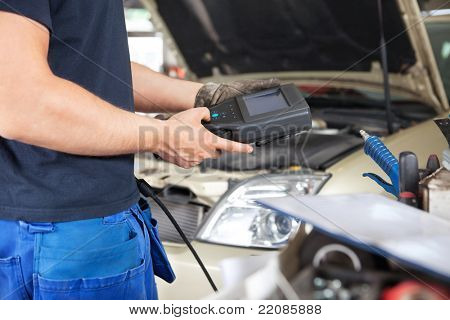 Mid section of mechanic holding a diagnostic tool