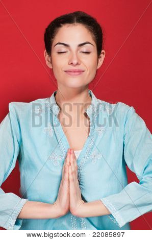 Smiling young woman with hands clasped against red background