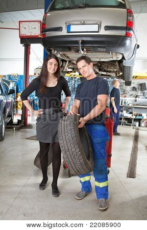 Full length portrait of female customer and mechanic holding tire in hand