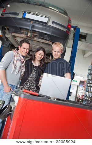 Smiling young couple standing with mechanic using laptop in auto repair shop