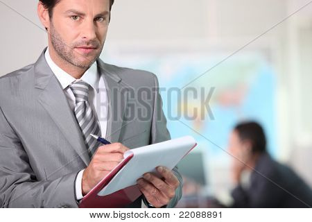 Businessman writing on a clipboard