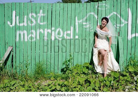 young happy bride near picture of angel wings on green fence
