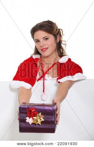 Woman dressed in Christmas outfit offering gift