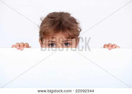 Girl peeking above a board