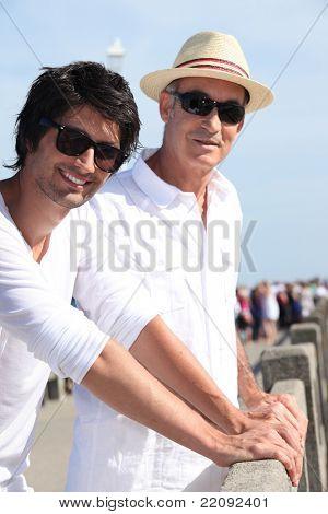 Dois homens de diferentes gerações em pé no sol