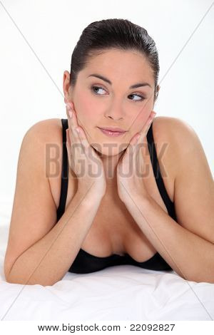 feminine woman in bra on a bed