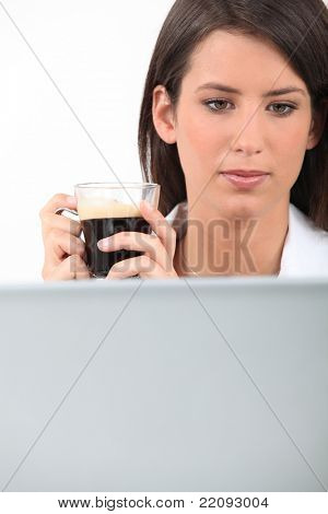 Woman drinking coffee while working at her laptop