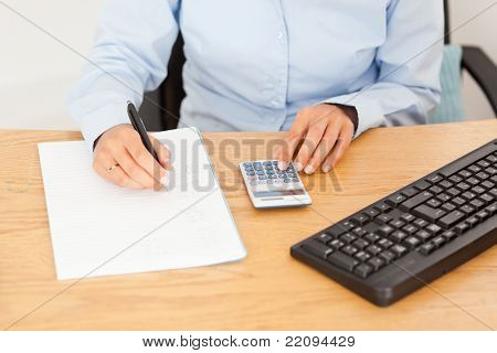 Female Accountant Writing Results On A Piece Of Paper