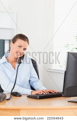 Secretary Answering The Phone While Typing On Her Keyboard