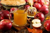 stock photo of cider apples  - A cup of hot apple cider caramel apple and apple pie surrounded by fresh fruits - JPG