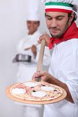 image of pizza parlor  - Pizza man and female cook in the background - JPG