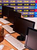 Monitor pc group in business interior office against stock market digital LED graph chart display . poster