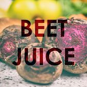 BEET JUICE words written on photo background of fresh red beets in kitchen or farms market. Raw orga poster