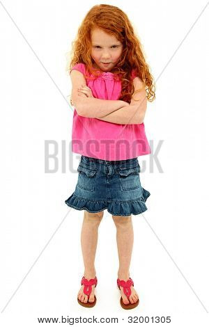 Adorable angry six year old girl with arms crossed in pink and blue over white. Curly long red hair.