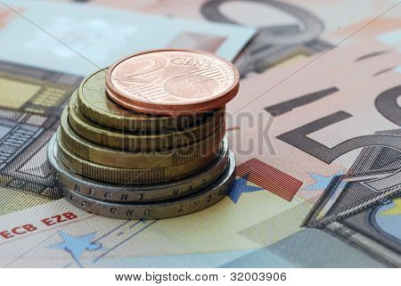 Closeup of a pile of coins resting on euro banknotes.