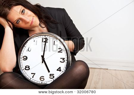 A Tired Woman Holding A Clock
