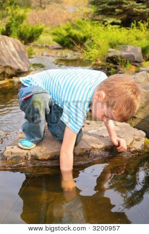 Boy Has Lowered Hand In Stream