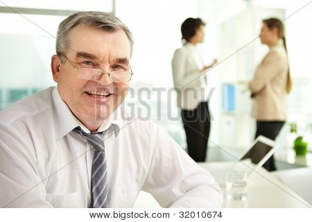 Mature businessman looking at camera in working environment