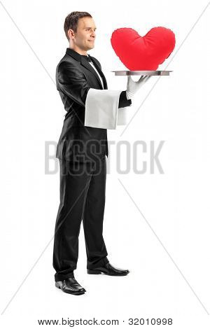 Full length portrait of a waiter holding a tray with a red heart shape on it isolated on white background
