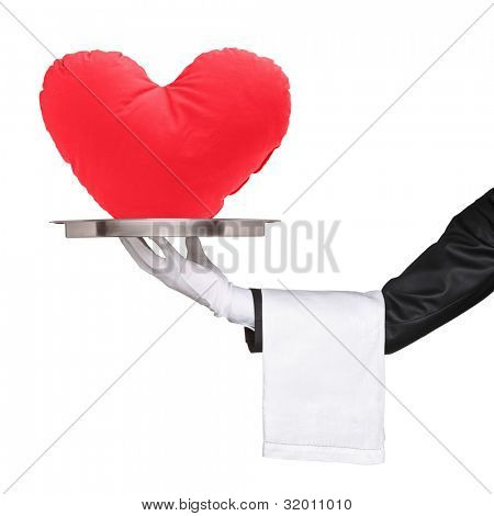 A studio shot of a hand holding a tray with red heart shaped pillow on it isolated on white background