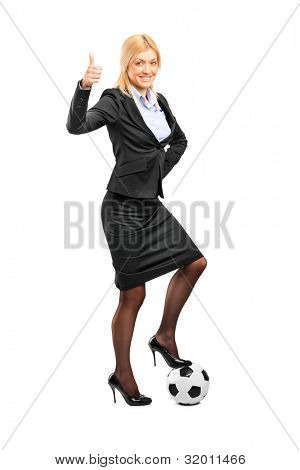 Full length portrait of a woman in high heels standing on a soccer ball and giving thumb up isolated on white background