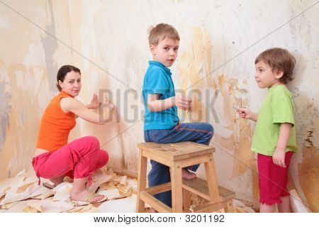 Children Help Mother Remove Old Wallpapers From Wall