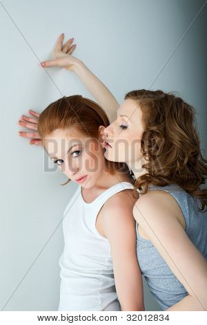 Two beauty woman in tank top near wall