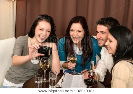 Cheerful young people enjoy drink after work at restaurant