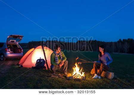 Tent camping car couple romantic sitting by bonfire night countryside