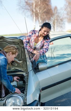 Starting broken car two women have problems looking under hood
