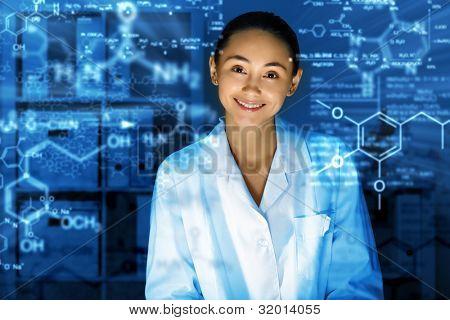 Jovem químico em uniforme branco, trabalhando no laboratório