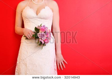 hands of bride wearing long white dress hold bouquet of roses on red background
