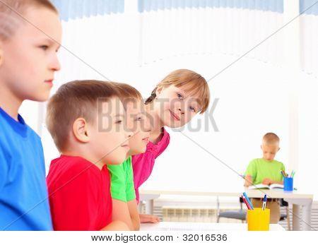 Groep klasgenoten staan in een rij in de klas